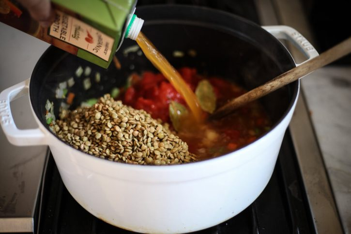 Green/Brown lentils and vegetable broth are added to a soup pot.