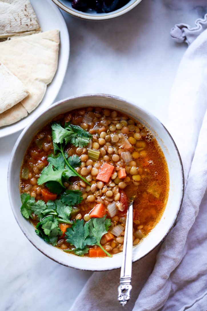 A bowl of vegan traditional Greek lentil soup garnished with cilantro sits on a marble countertop next to pita bread and olives.