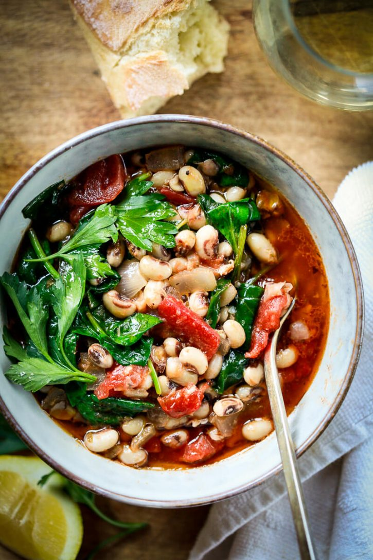 A bowl filled with healthy vegan stewed black eyed peas with tomatoes, broth, spinach and lemon.