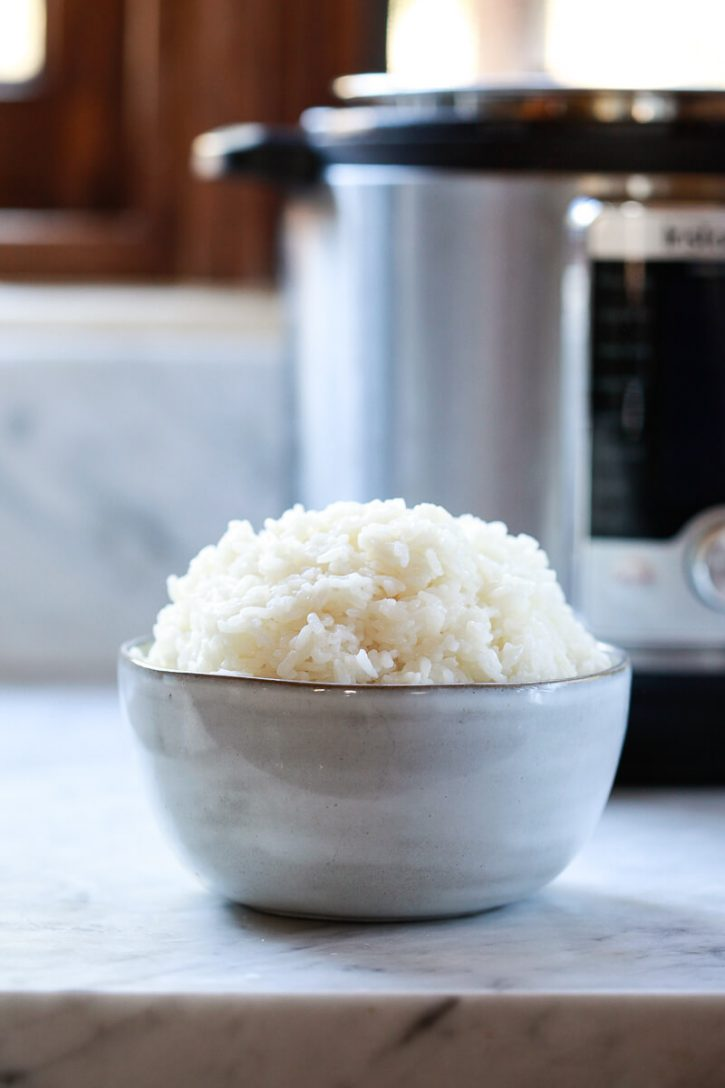 A bowl of perfect sushi rice sits on a kitchen counter in front of an Instant Pot pressure cooker.