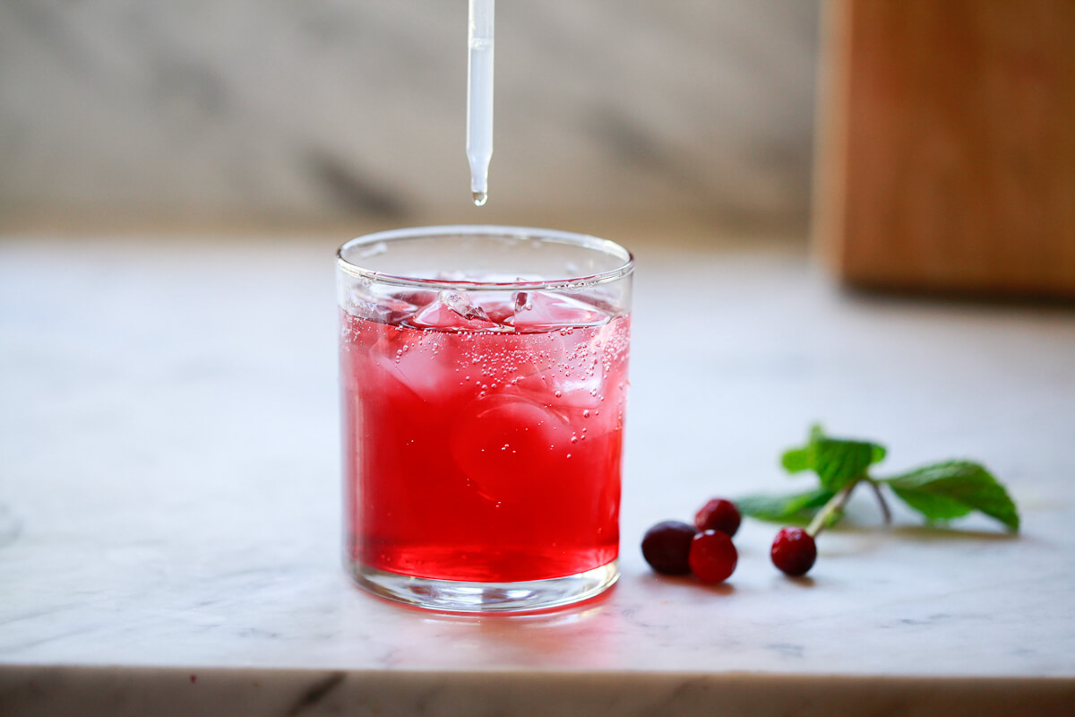 Liquid stevia is added to a glass of cranberry detox water.