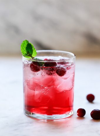 A red cranberry detox water drink in a clear glass with ice and cranberries.