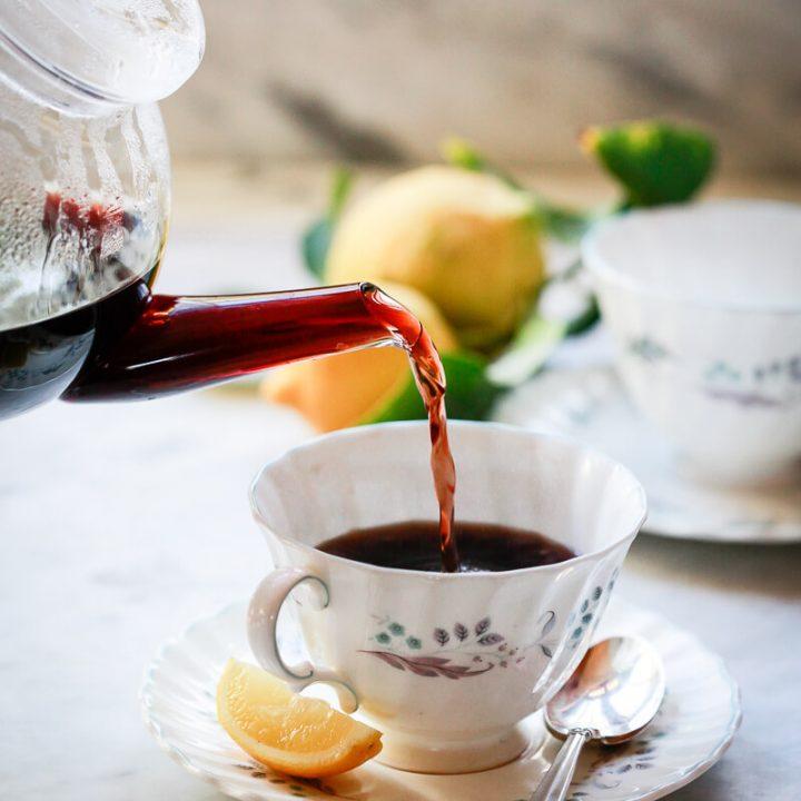 A teapot pours homemade elderberry tea into a teacup.
