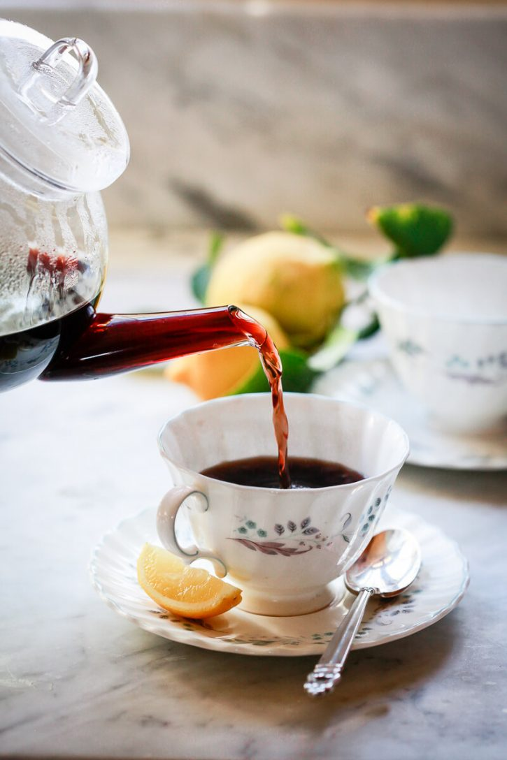 Homemade elderberry tea pours from a teapot into a teacup. This homemade elderberry tea is a natural remedy for cough, cold, and flu.