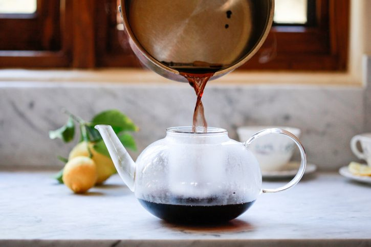 A saucepan of homemade elderberry tea is poured through a strainer in a teapot.