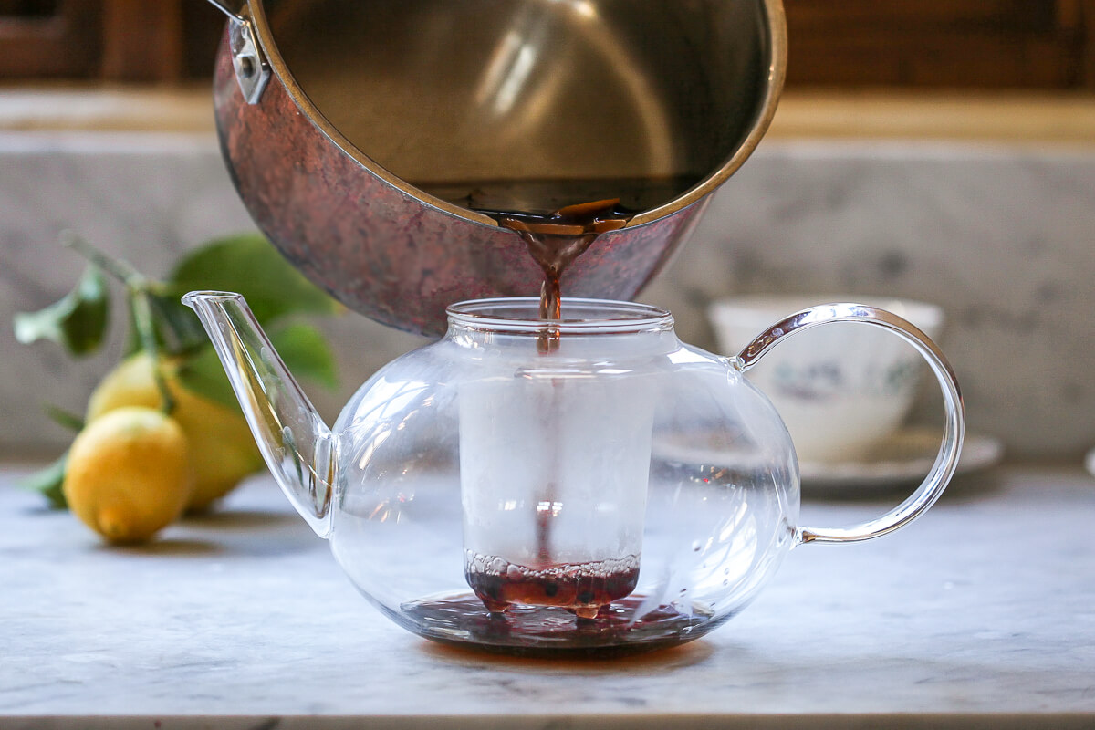 Homemade elderberry tea is strained into a teapot.