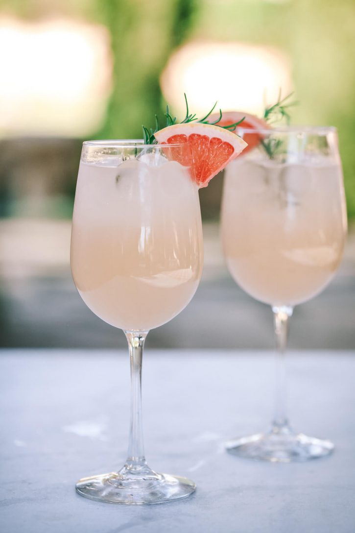 A beautiful photograph of two glasses filled with fresh grapefruit soda and ice, garnished with pink grapefruit wedges and rosemary. This grapefruit soda is perfect for cocktails like tequila paloma.
