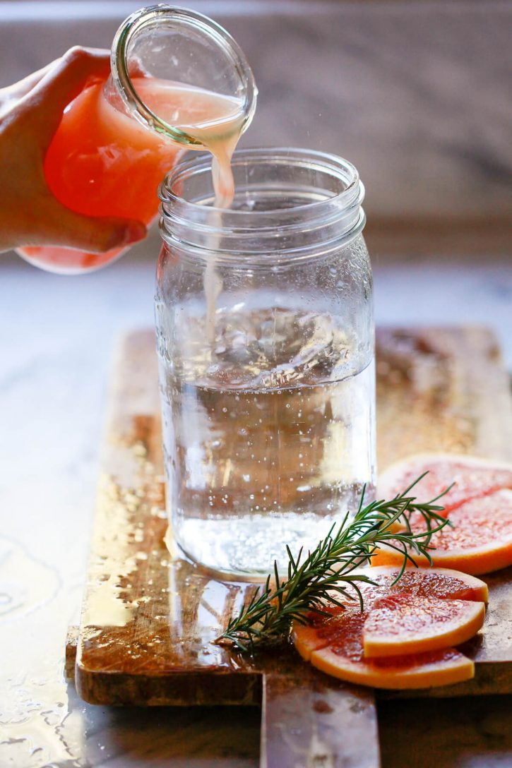 Fresh grapefruit juice is poured into a mason jar filled with sparkling water to make sugar free grapefruit soda.