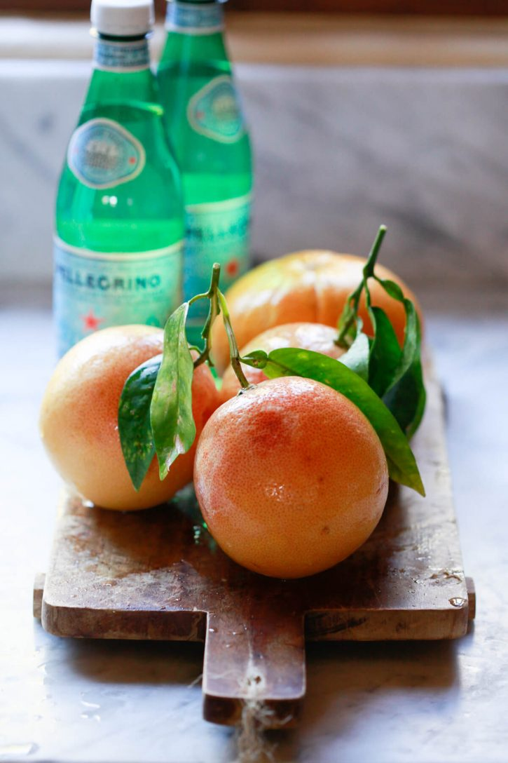 Homegrown grapefruits and bottles of San Pellegrino water on a marble countertop.