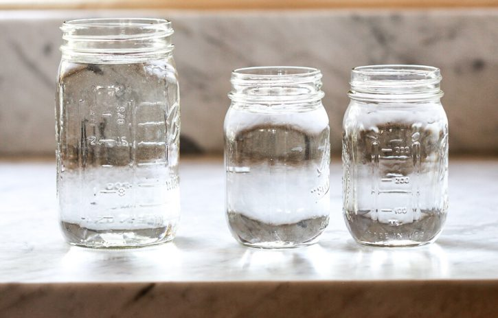 Two pint sized mason jars sit next to a larger quart sized mason jar to show that there are 2 pints in a quart.