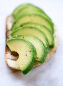 A piece of toast topped with perfectly sliced avocado.