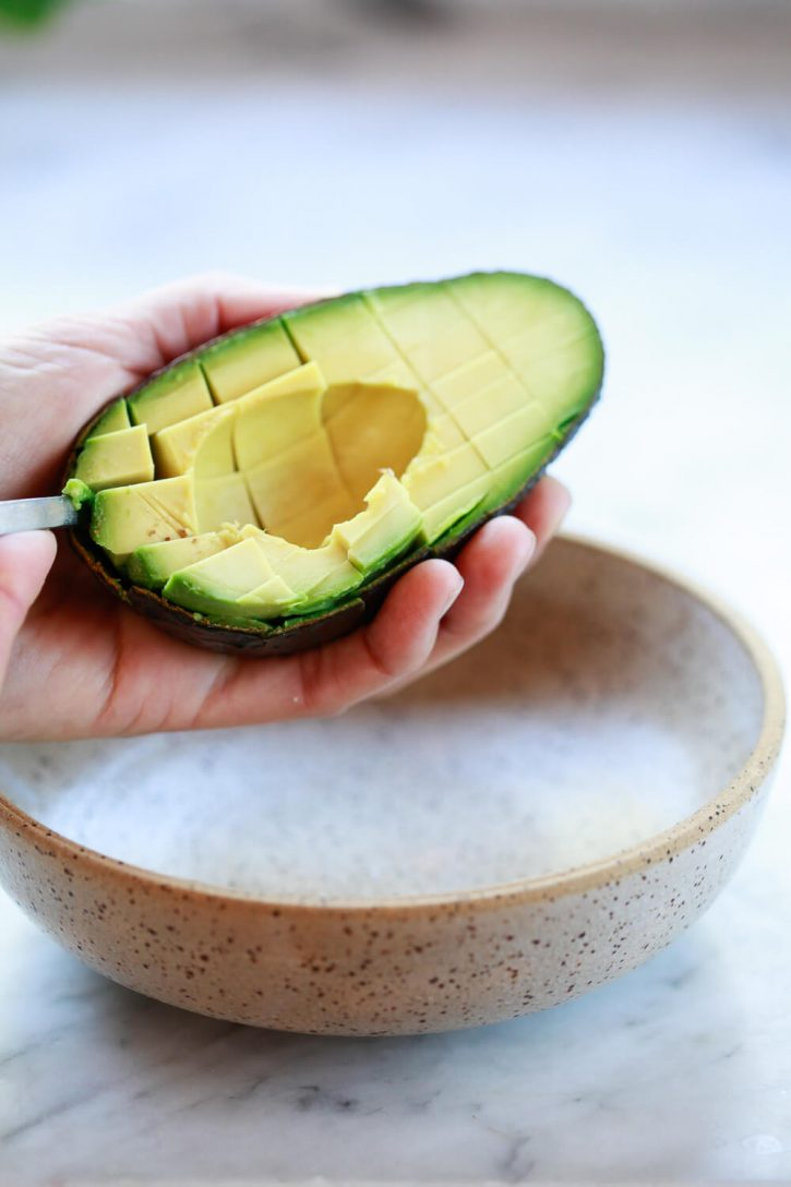 Close-up of a spoon scooping avocado cubes out of the skin into a bowl.