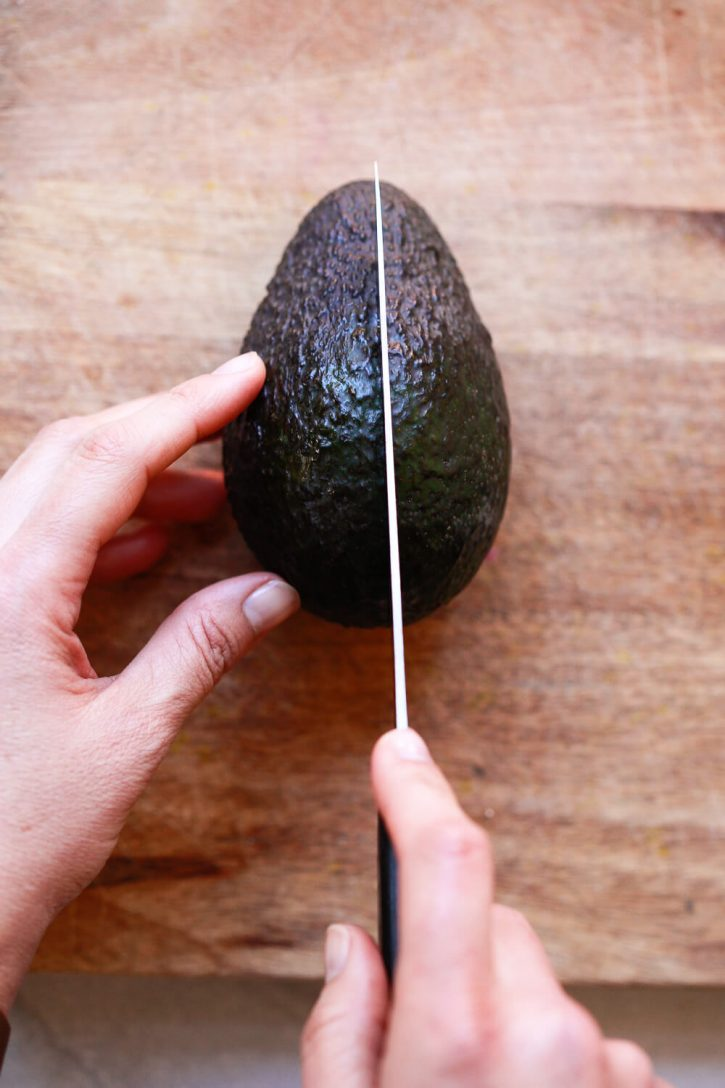 A photo of hands cutting a Haas avocado in half lengthwise with a knife.