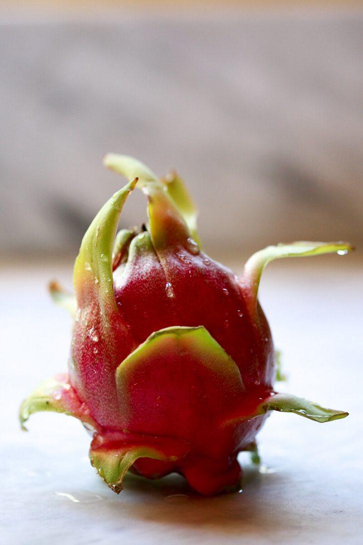 A whole red pitaya fruit sits on a white kitchen counter.