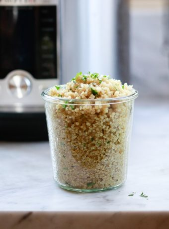 A glass jar filled with perfectly cooked quinoa topped with herbs. An Instant Pot in the background.