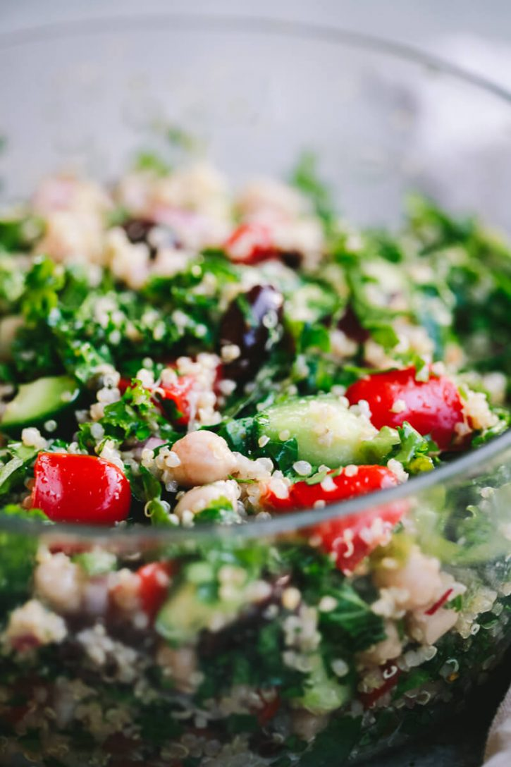 A close-up photo of a quinoa salad with kale, chickpeas, tomatoes, cucumbers, olives, and herbs.