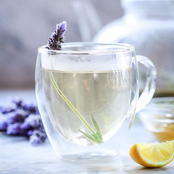 A cup of lavender tea in a glass cup garnished with a sprig of fresh lavender.