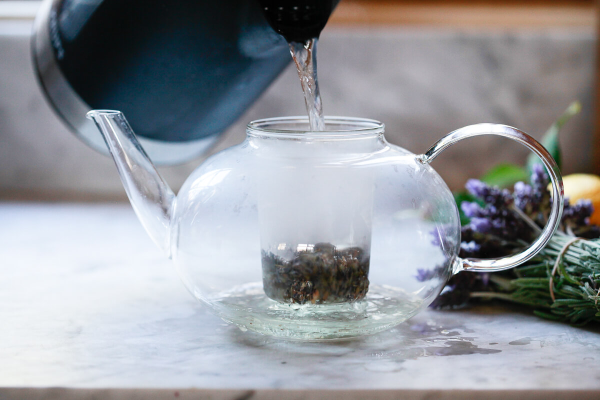 Boiling water is poured over dried lavender in a glass teapot infuser.