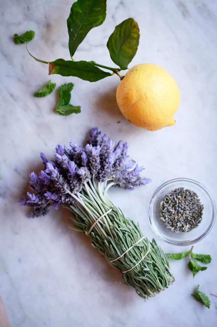A bunch of organic fresh culinary lavender sits on a counter with a lemon and a small bowl of dried culinary lavender.