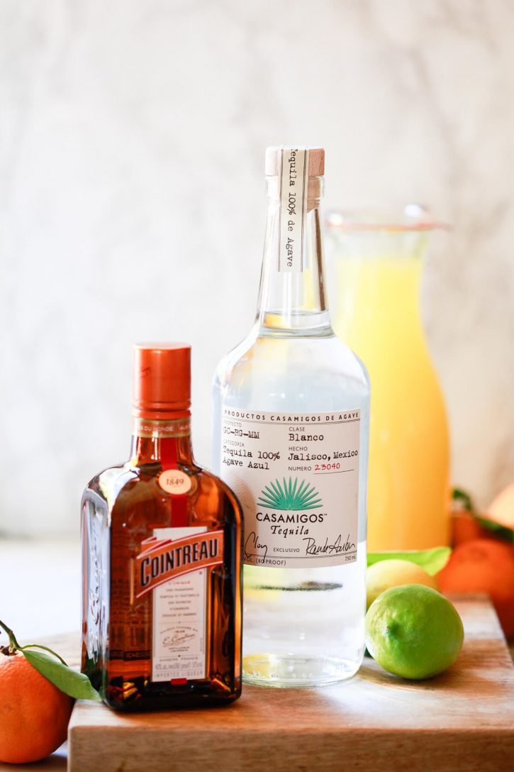 A bottle of Casamigos tequilla and a bottle of Cointreau sit on a kitchen counter with fresh citrus.