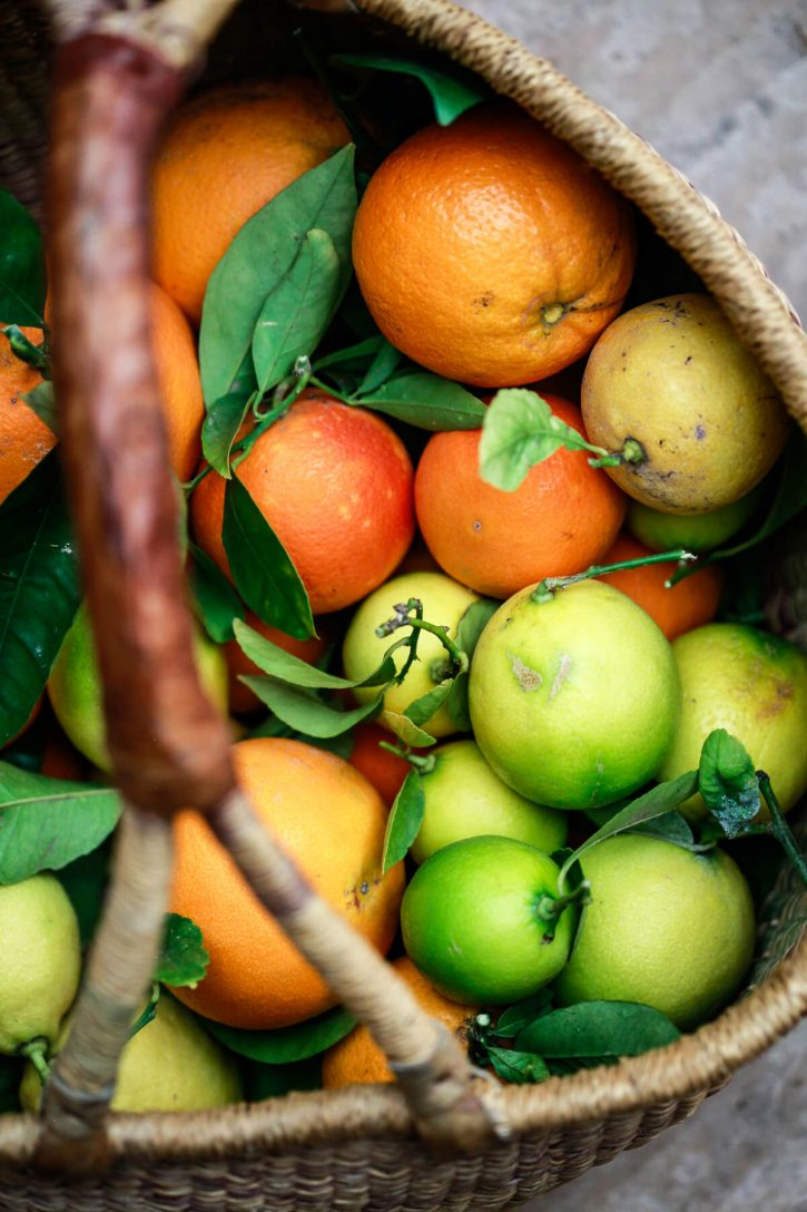 A photo of a basket filled with just picked limes, oranges and lemons. Backyard citrus.