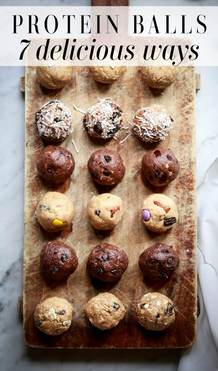 Photo of six different flavors of peanut butter protein balls on a cutting board, including: oatmeal raisin, double chocolate, trail mix, mocha, almond joy, and peanut butter oatmeal.