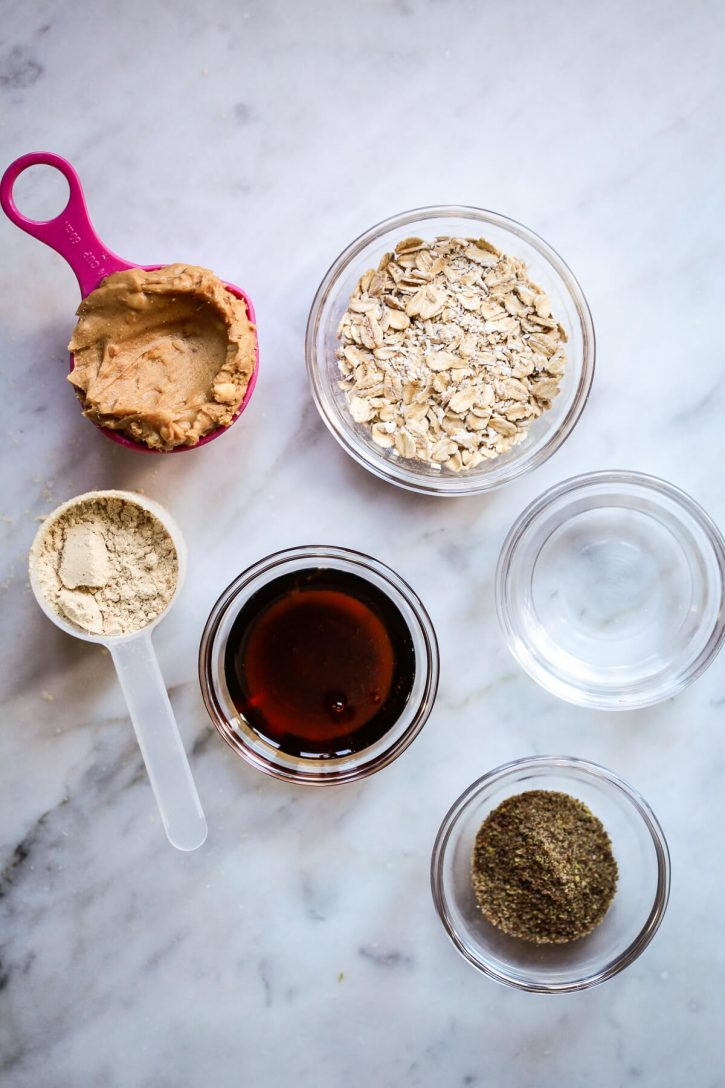 5 ingredients for protein balls on a white marble countertop. Oats, peanut butter, protein powder, maple syrup, flax meal, and water.