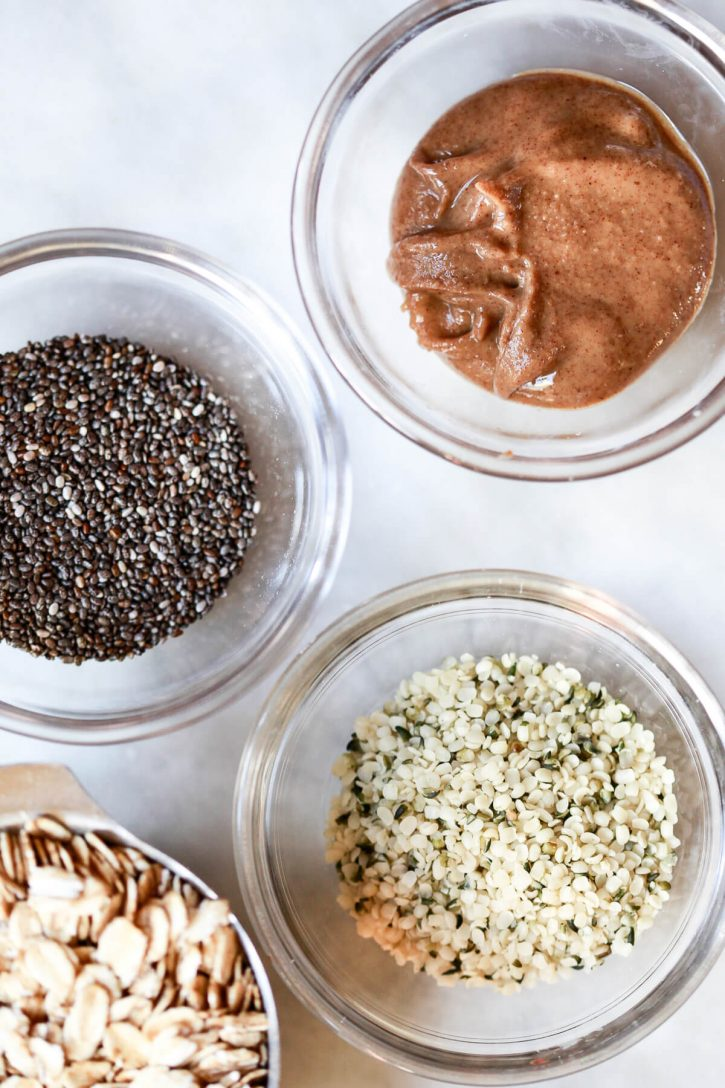 Small bowls filled with chia seeds, hemp seeds, and almond butter on a kitchen counter.