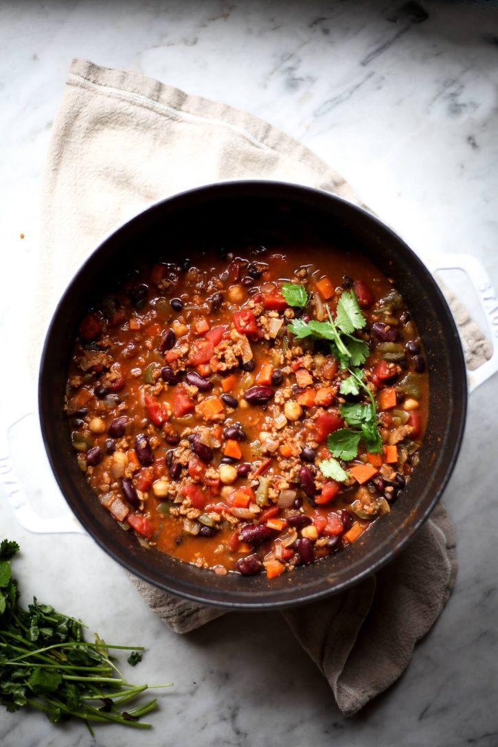 An overhead photo of a pot of vegan bean chili garnished with cilantro.