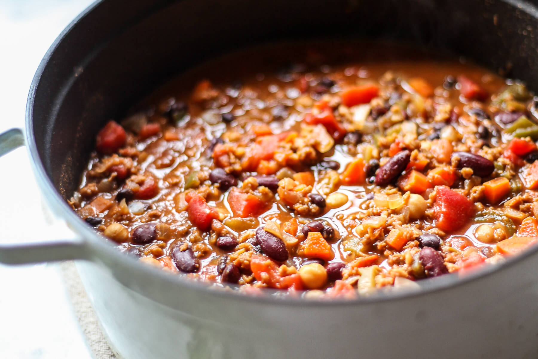 A close up photograph of vegan chili with chickpeas and beans that's finished simmering in a pot.