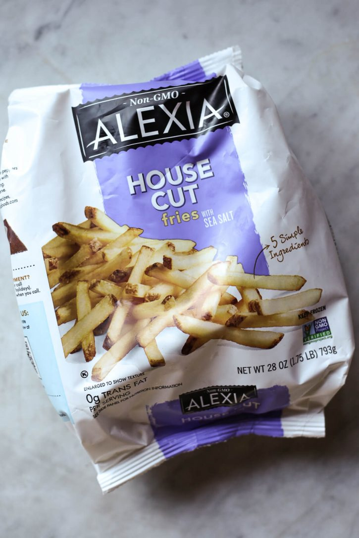 A bag of Alexia house cut frozen french fries on a marble countertop.