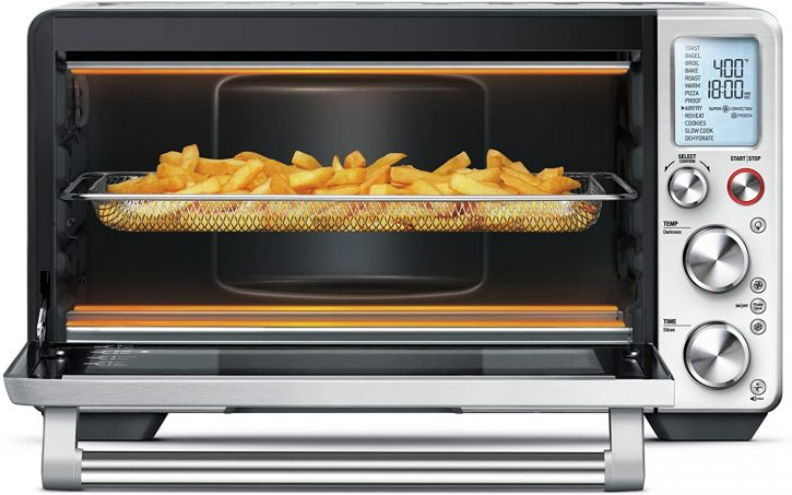 A photo of a Breville smart oven with french fries cooking inside an air fryer basket.