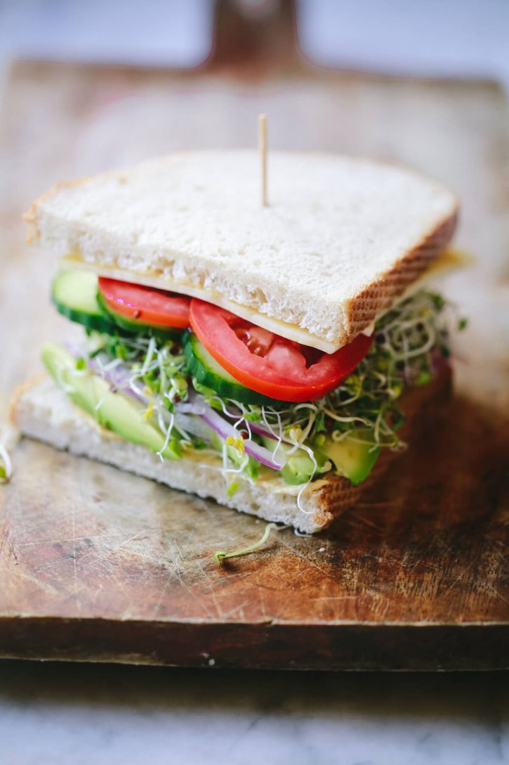 A veggie sandwich with avocado, onion, broccoli sprouts, cucumber, and tomato.