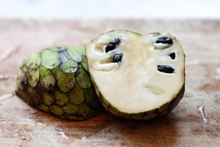 Half a Cherimoya sits on a cutting board. This is a delicious exotic fruit.