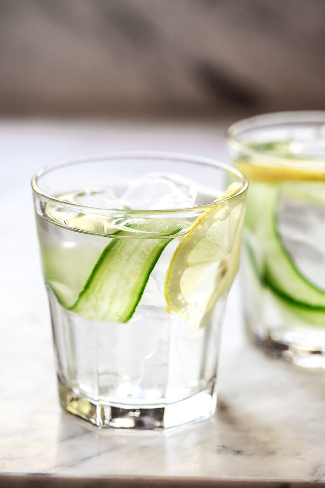 A close-up photo of two glasses filled with ice, water, lemon and cucumber ribbons. A beautiful and healthy cucumber water recipe for weight loss, detox, and clear skin. .