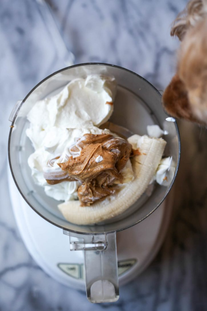 Greek yogurt, peanut butter, and banana are seen in a food processor to make Frosty Paws homemade dog ice cream. A dog looks in.