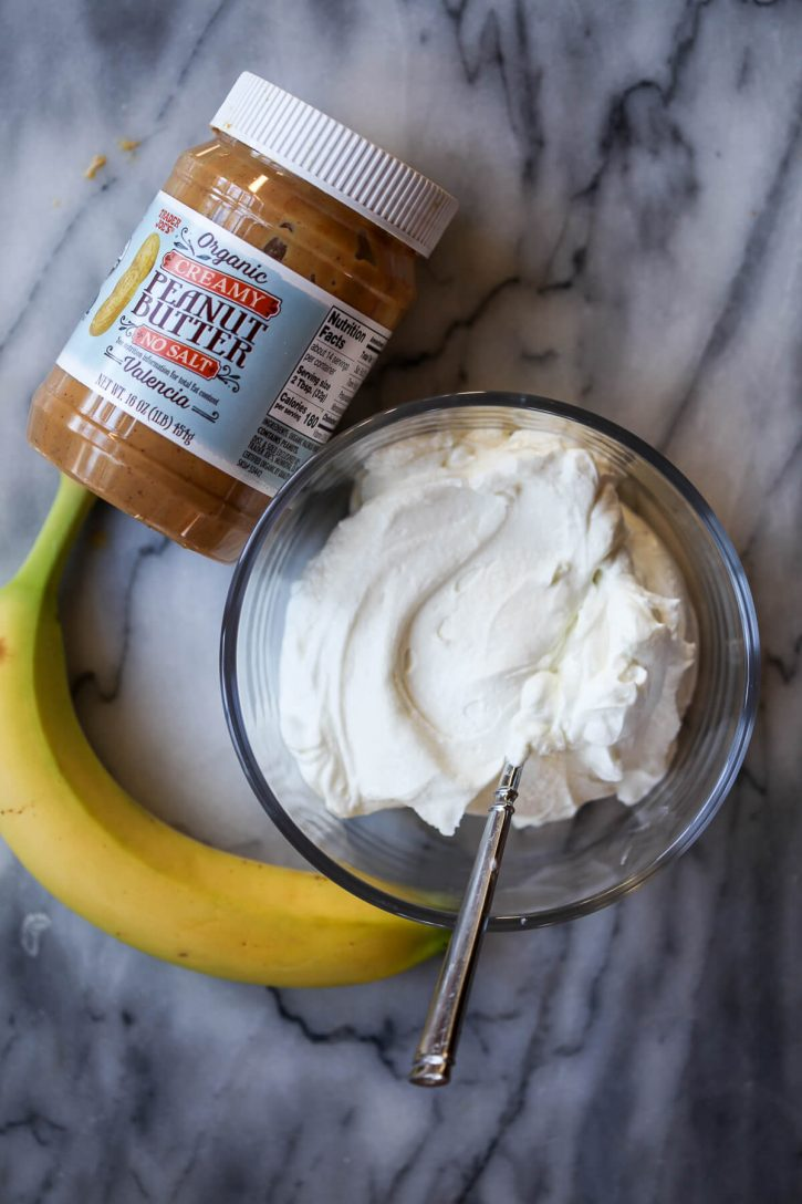 The simple ingredients for homemade dog ice cream on a marble counter: yogurt, peanut butter, and banana.