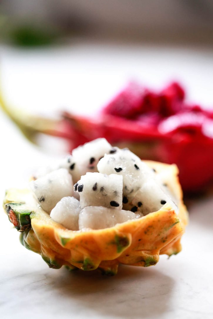 Close up photograph of half a yellow dragon fruit with white flesh and black seeds cut into cubes.