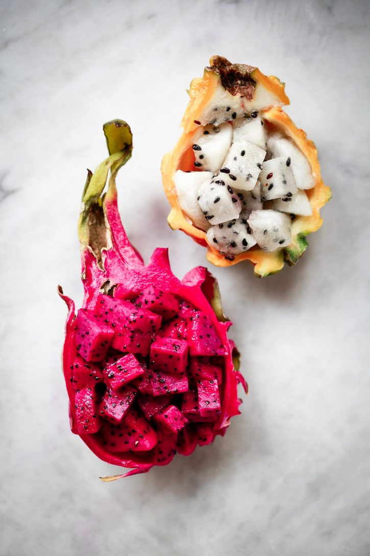 Photograph of red and yellow dragon fruit halves on a marble countertop. An example of beautiful exotic fruits.