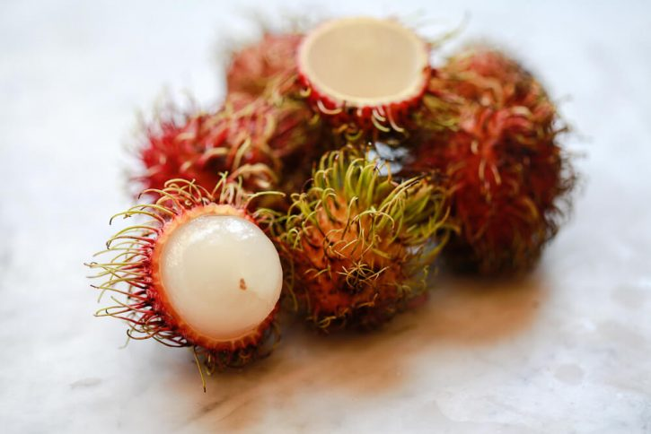A pile of rambutan sits on a marble countertop. This exotic fruit is harry on the outside and juicy on the inside.