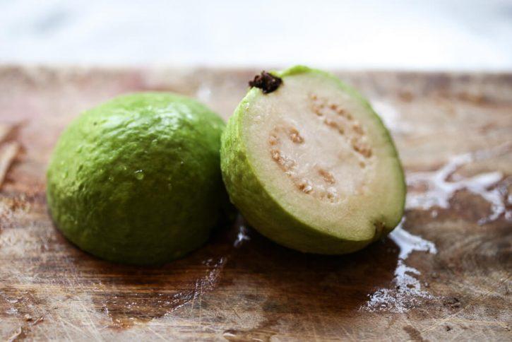 A Thai white guava cut in half on a cutting board.