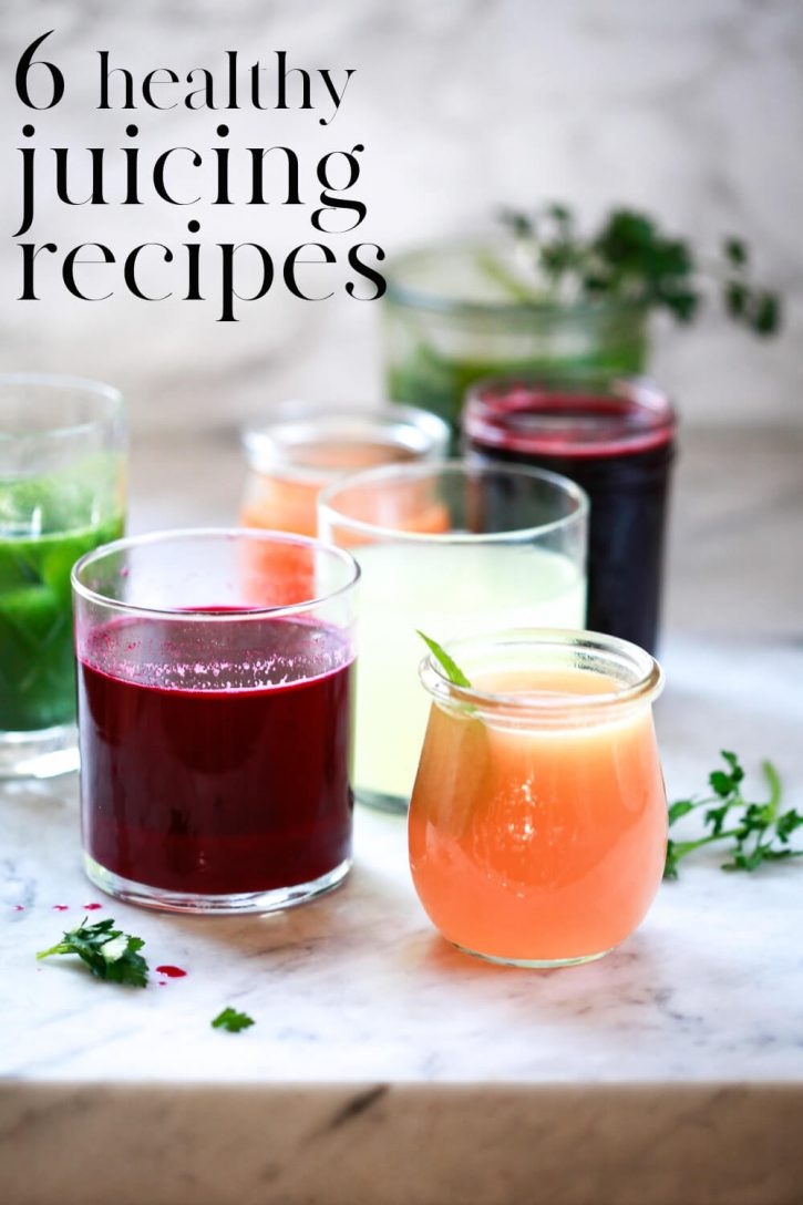 "A beautiful photography of 6 glasses filled with colorful juices on a white countertop. Text overlay reads, ""6 healthy juicing recipes."""