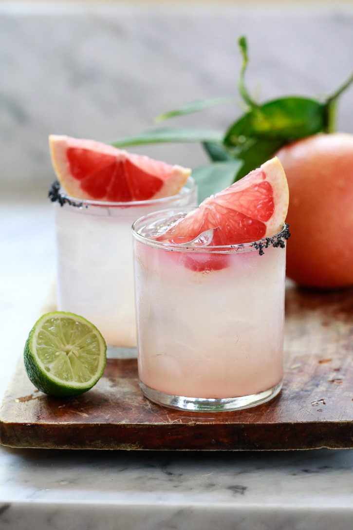 Two paloma cocktails made with grapefruit soda and tequila in a white kitchen.