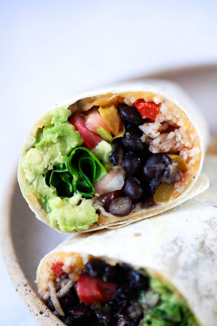 A close-up photo of a vegan burrito made with black beans, Spanish rice, lettuce, salsa, and guacamole.