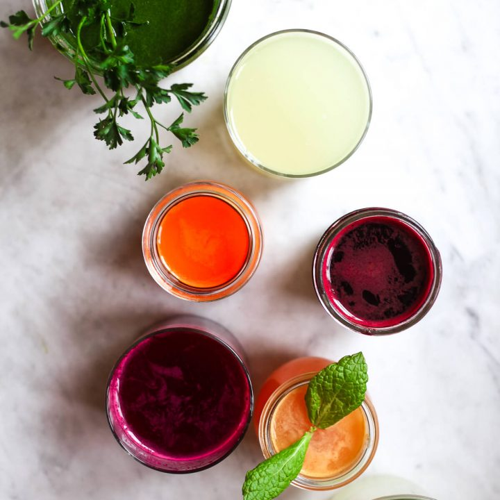 Six glasses of colorful freshly pressed juices.