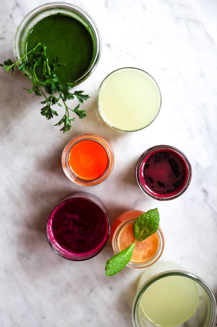 An overhead photo of colorful fresh juices in glasses on a white kitchen counter. These look like healthy juicing recipes.