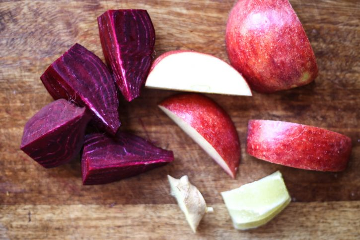 A raw beet, apple, ginger, and lemon on a cutting board for juicing.
