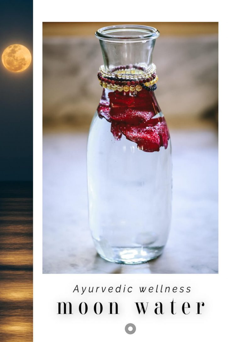 A carafe of homemade full moon water with crystals and rose petals sits on a marble countertop.