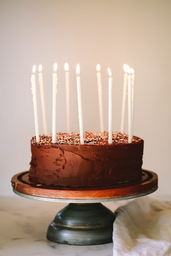 A vegan birthday cake coated in vegan chocolate frosting and topped with white candles.