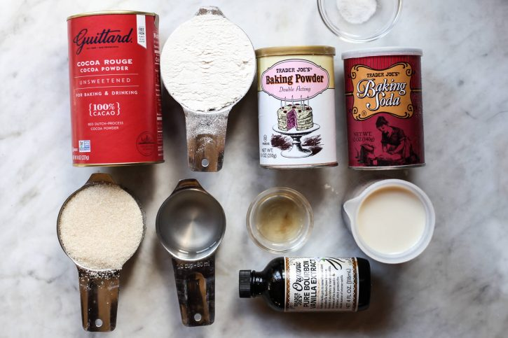 The ingredients for dairy-free, eggless, cupcakes on a countertop: Dutch process cocoa powder, flour, baking powder, baking soda, salt, sugar, coconut oil, vinegar, milk, and vanilla.